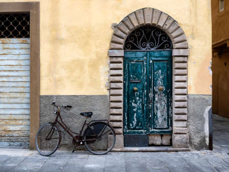 lucca: Fringed door and bike in Lucca, Italy