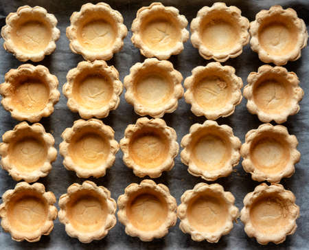 Tartlets empty in many rows on a baking sheet Stock fotó