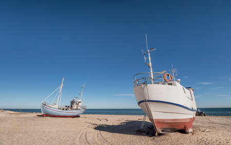 Coastal fishing boats on the beach at Thorup Strand at the North Sea in Denmark
