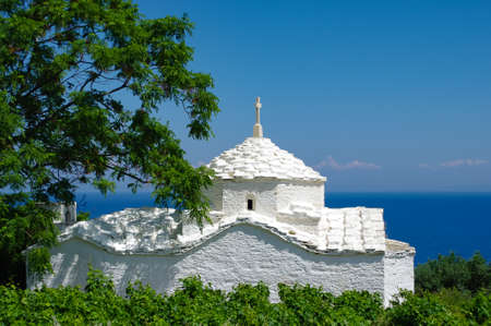 White church in front of the blue sea, framed by bushes and a tree, Samos, Greece Reklamní fotografie
