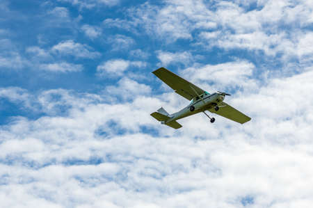 Single engine sport airplane in the air in front of clouds