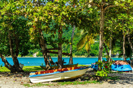 Boats lying in the sand under trees at a beach on Guadeloupe