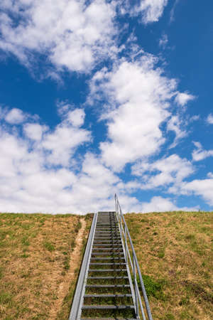 Metal staircase to the top of a dike, yellow grass and blue sky with white clouds, Lower Saxony, Germany