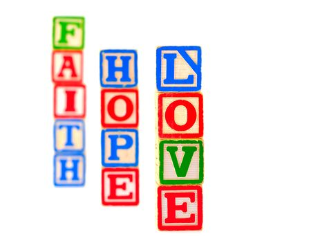 hope: The words FAITH, HOPE and LOVE spelled out using some old alphabet blocks. Stock Photo