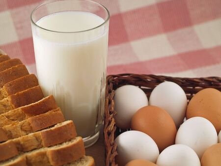 A glass of milk, a loaf of wheat bread and brown & white eggs - grocery staples.          Stock fotó