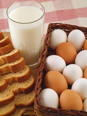 A glass of milk, a loaf of wheat bread and brown & white eggs - grocery staples.          photo