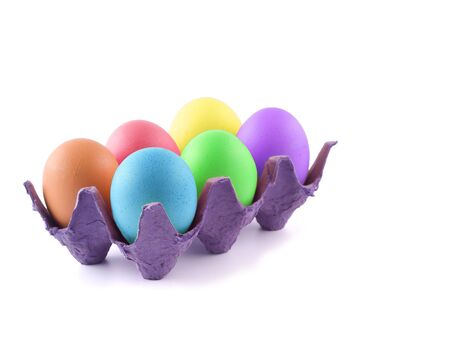 Six pastel colored Easter eggs in a purple carton isolated on white. photo