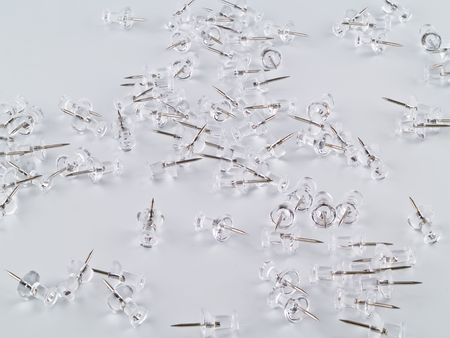A bunch of clear thumb tacks on a blank background, not pure white.