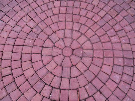 A spiral pattern of red brinks on a sidewalk.