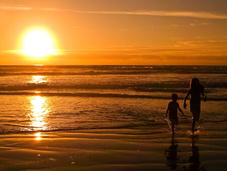 With the sun setting, young people are playing at the beach on the Oregon Coast. photo