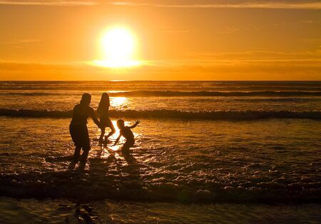 With the sun setting, young people are playing at the beach on the Oregon Coast. Stock Photo
