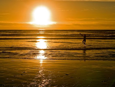 With the sun setting, a young girl is playing at the beach on the Oregon Coast. photo