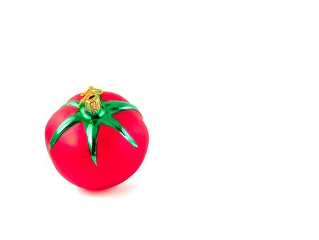 A glass, Christmas ornament in the shape of a red, ripe tomato. photo