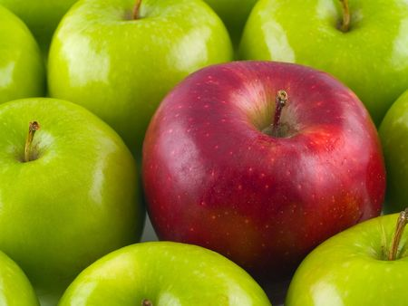 midst: Background of Green Apples with a single Red Delicious in the midst.