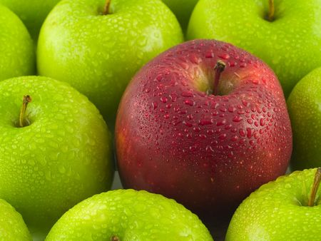 Background of Wet Green Apples with a single Red Delicious in the midst. Фото со стока