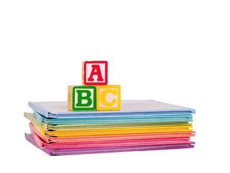 ABC Blocks dispos�es sur une pile de couleur arc-en-ciel de livres pour enfants. Isolated on white. Banque d'images
