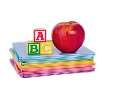 ABC Blocks and a Red Apple arranged on a stack of rainbow colored childrens books.  Isolated on white.A