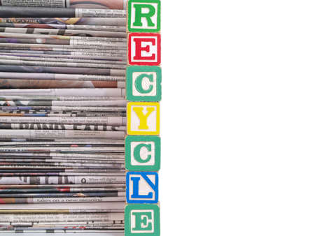 Old newspapers stacked filling half the frame and Recycle is written in Block Letters. photo