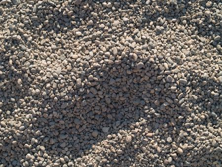 shadowy: Sunlit playground pea gravel with shadows and footprints Stock Photo