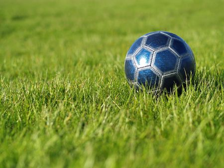 A blue soccer ball on a field of green grass on a bright, sunny day Stock Photo - 5000252