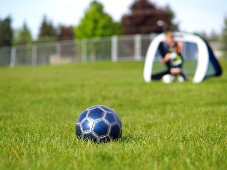 A blue soccer ball on field of green grass on a sunny day with kids in the background. Stock Photo - 5000242