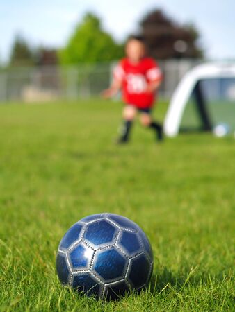 A blue soccer ball on field of green grass on a sunny day with kids in the background. Stock Photo