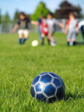children at play: A blue soccer ball on field of green grass on a sunny day with kids in the background. Stock Photo