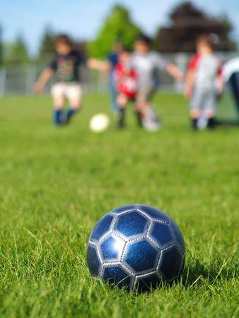 football play: Un pallone da calcio azzurro sul campo di erba verde, in una giornata di sole con bambini in background. Archivio Fotografico
