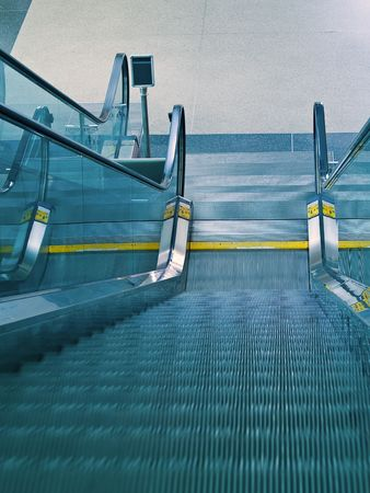 An airport escalator from the top landing showing motion blur photo