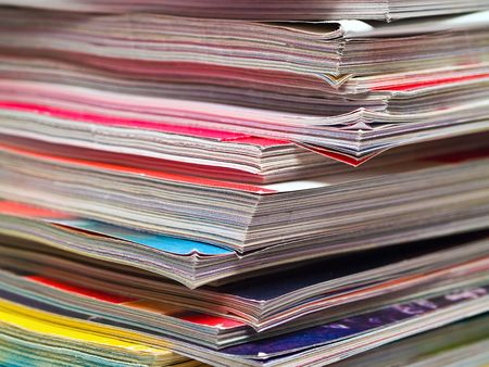 uneven edge: An uneven stack of magazines filling the frame from top to bottom focus on corner edge