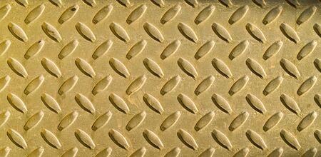 Diamond gold toned metal background texture illuminated by sunlight
