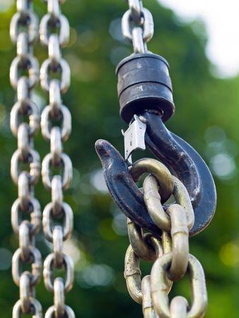 polea: Gran gancho de metal y las cadenas de conexi�n a una polea Foto de archivo