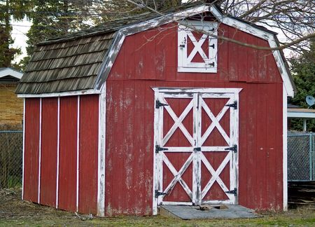 Weathered little red barn with white trim photo