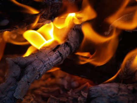Flames in a fire pit with glowing embers