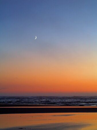 Moonrise over the ocean with a beach foreground         photo