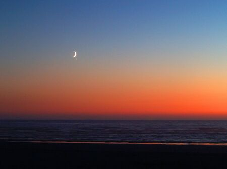 crescent: Moonrise over the ocean with a beach foreground