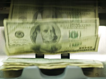 An electronic money counter processing US $100 bills photo