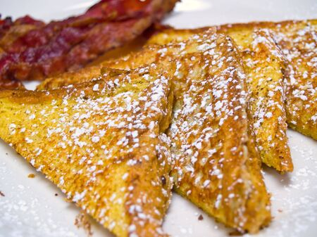sugar powder: French Toast dusted with Powdered Sugar and Bacon