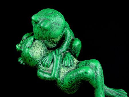 Two Green Frogs in a Romantic Embrace Statue Stock Photo