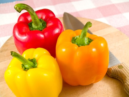 Bell Peppers on a Wooden Cutting Board with Knife photo