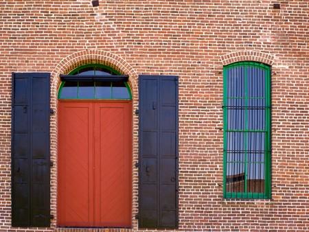 puertas viejas: Muro de ladrillo rojo con una red de puerta y ventana  Foto de archivo
