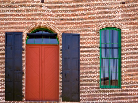 Red Brick Wall with a Red Door and Window Stock Photo
