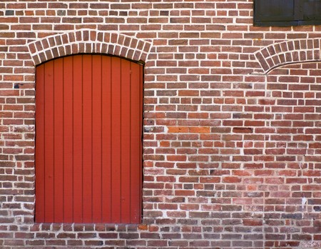 Red Brick Wall with a Red Door and Window photo