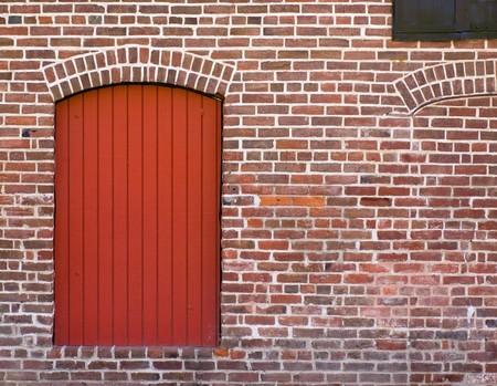 Rode bak stenen muur met een rode deur en venster Stockfoto