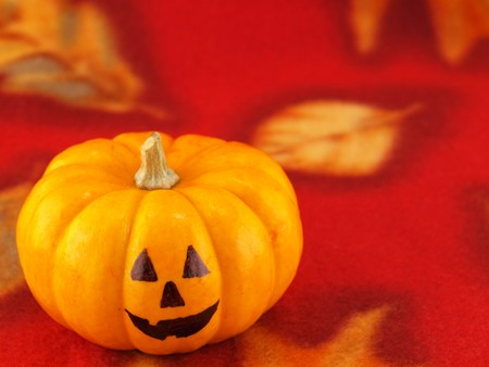 Mini Pumpkins with Funny Faces on a Red Autumn Cloth Background Stock Photo