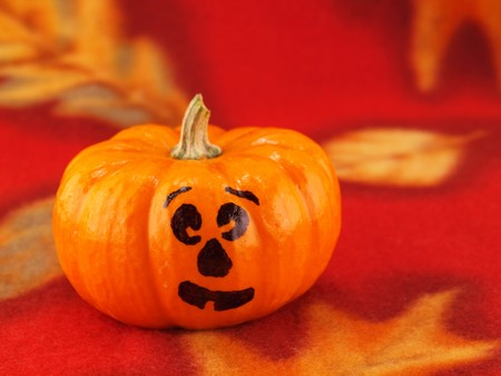 Mini Pumpkins with Funny Faces on a Red Autumn Cloth Background photo