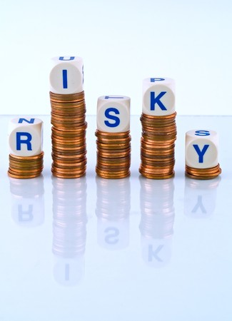 Letter Dice Spelling Risky atop Penny Stacks Stock Photo