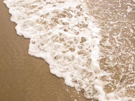 Foamy Ocean Shoreline at a Sunny Beach  photo