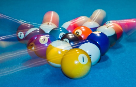 Billiards balls with motion on a green pool table photo