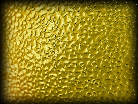 Water droplets formed from condensation inside a gold bottle with dark edge border